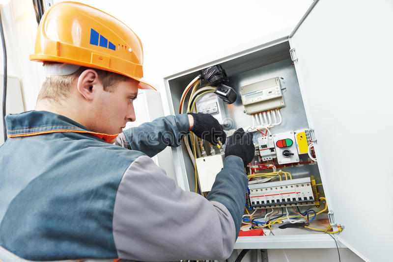 Electrician engineer worker. Young adult electrician builder engineer screwing equipment in fuse box stock photos