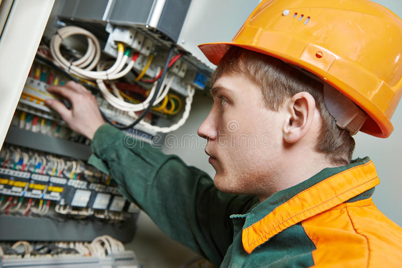 Electrician engineer worker. Young adult electrician builder engineer switching actuator equipment in distribution fuse box stock image