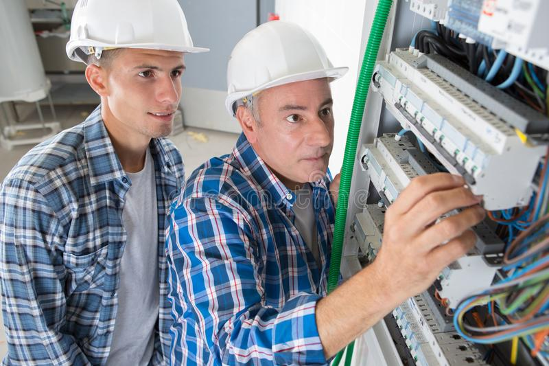 Electrician engineer workers in front fuse switch board royalty free stock photo