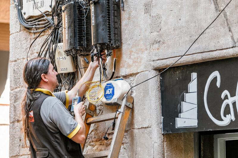 electrician engineer works with cables in electric network at city street stock images