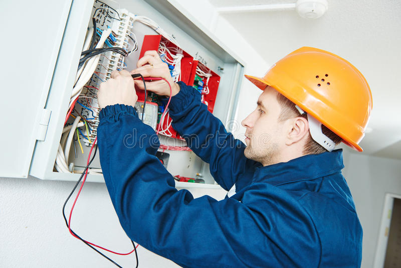 Electrician examining current voltage with screwdriver tester. Electrician works. male technician examining electric equipment with screwdriver meter tester in royalty free stock photos