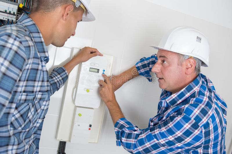 Electrician explaining electric meter to apprentice stock photography