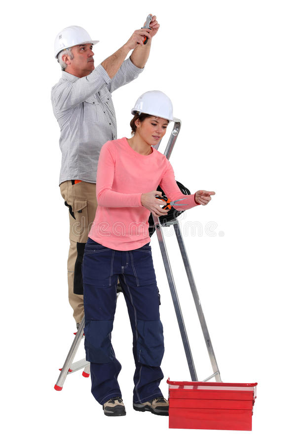 Electrician and female apprentice royalty free stock images