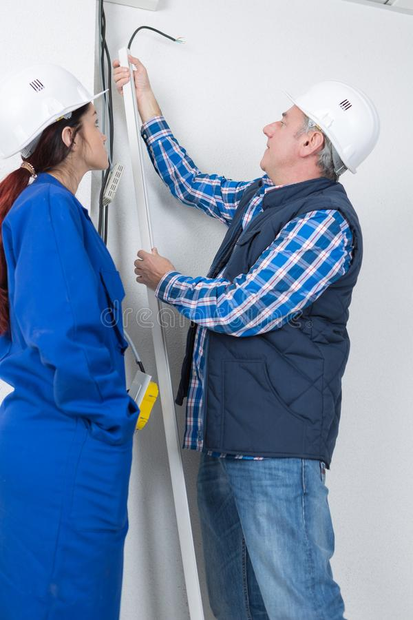 Electrician with female apprentice working in new home royalty free stock photo