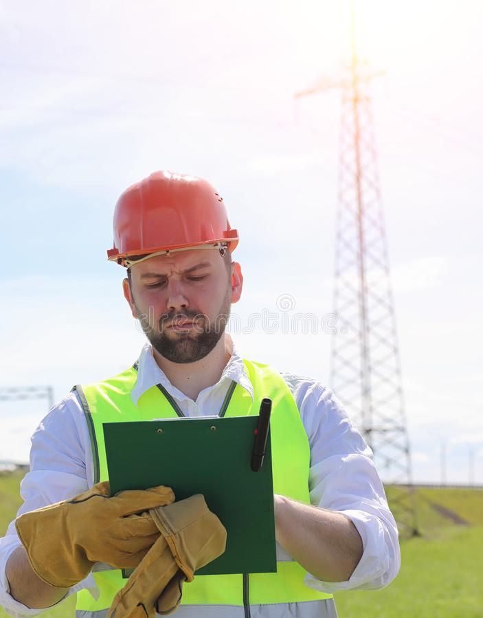 An electrician in the fields near the power transmission line. T. He electrician manages the process of erecting power lines. The mechanic in a helmet and a royalty free stock photography