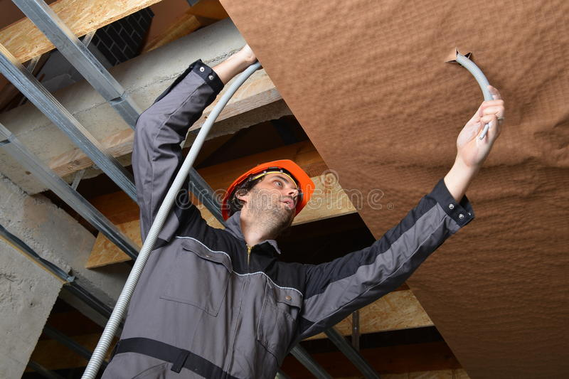 Electrician fitting a cable. For ceiling light stock photo