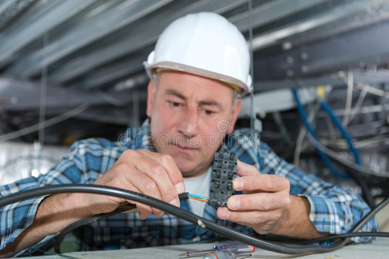 Electrician fitting cable for ceiling light stock photos
