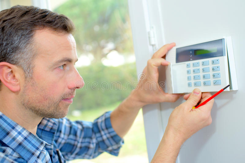 Electrician fitting intrusion alarm royalty free stock image