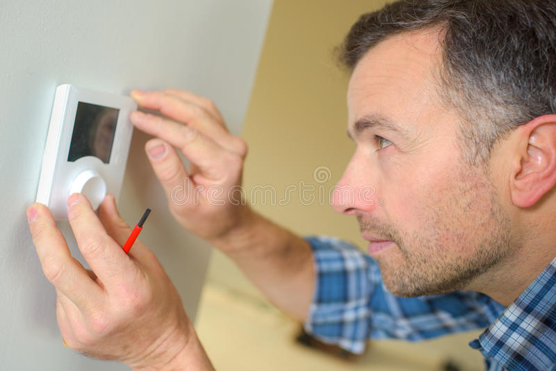Electrician fitting thermostat system royalty free stock image