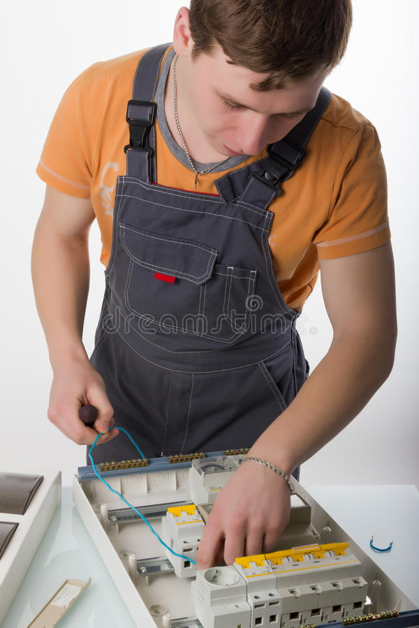 Electrician fixing cable in domestic electrical box royalty free stock images