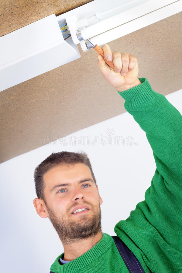 Electrician fixing ceiling light stock photography