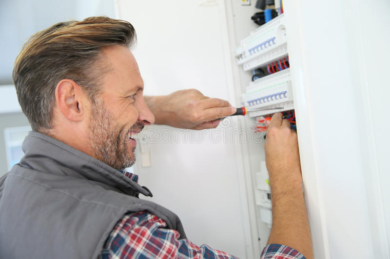 Electrician fixing home panel box. Electrician fixing electric panel in private home stock photo