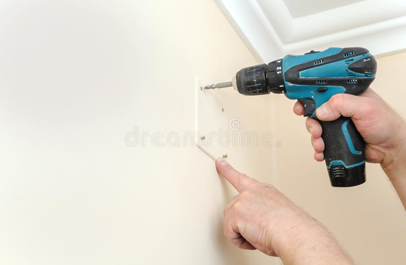 Electrician is fixing the lid on the switching box. royalty free stock image