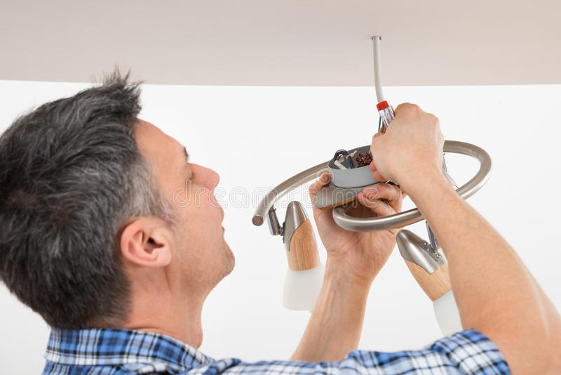 Electrician fixing light on ceiling stock photos