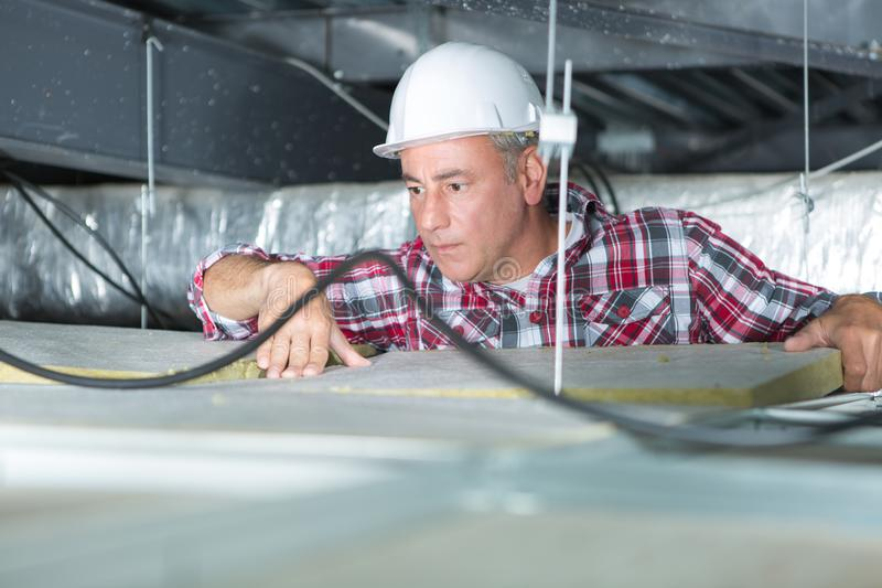 Electrician fixing neon on ceiling. Electrician fixing neon on the ceiling royalty free stock photo