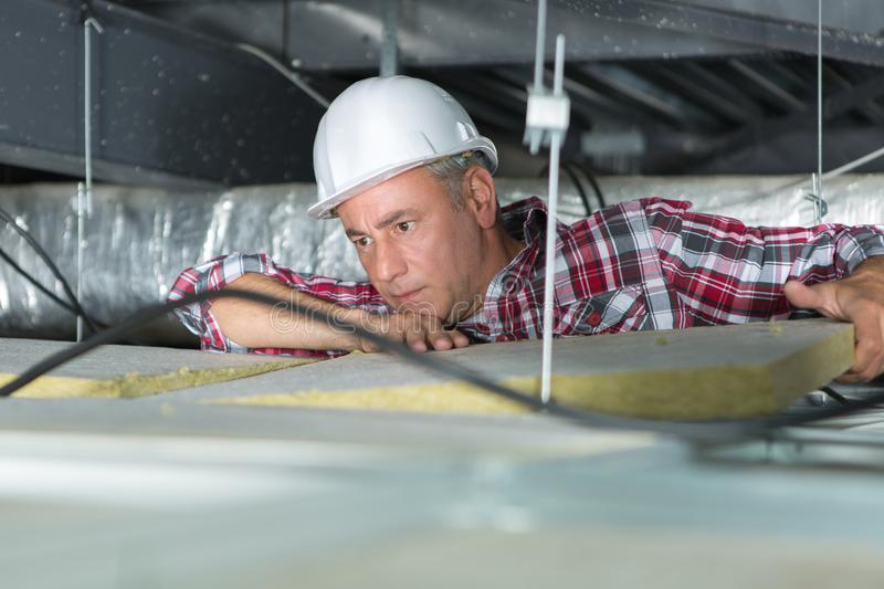 Electrician fixing neon on ceiling stock images