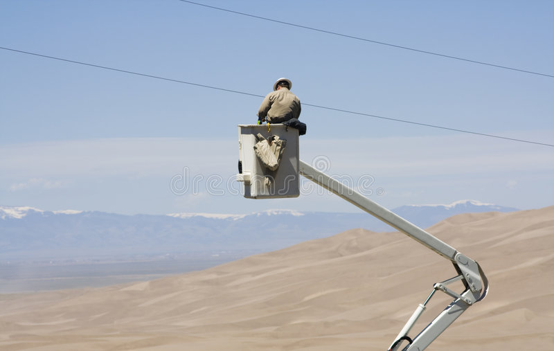 Electrician fixing power line. Electrician fixing damaged power lines royalty free stock images