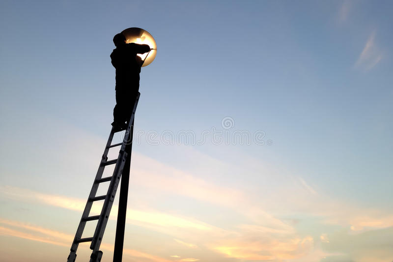 Electrician fixing street light bulbs and climbing on a ladder stock image