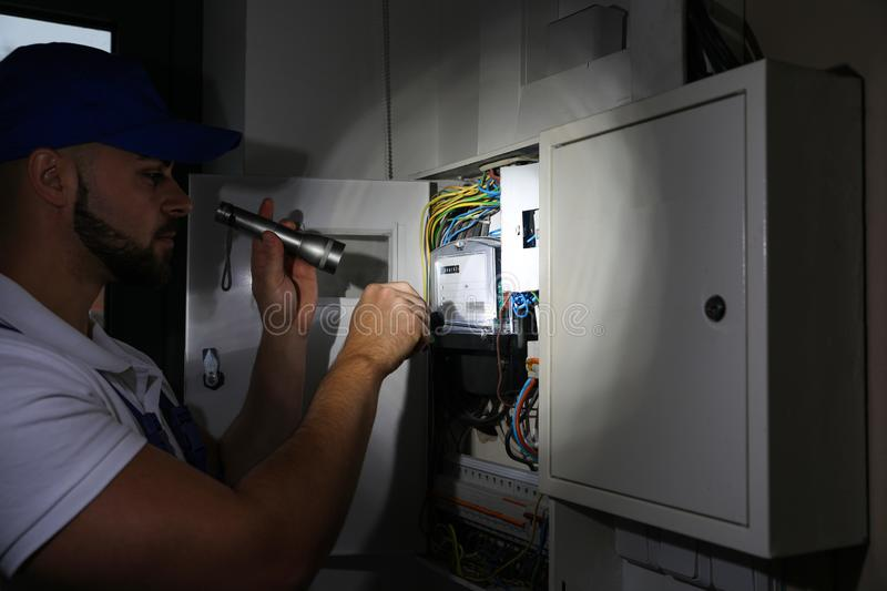 Electrician with flashlight fixing electric panel royalty free stock images