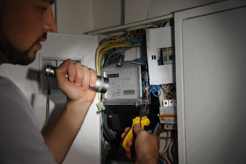 Electrician with flashlight fixing electric panel indoors. Closeup stock images