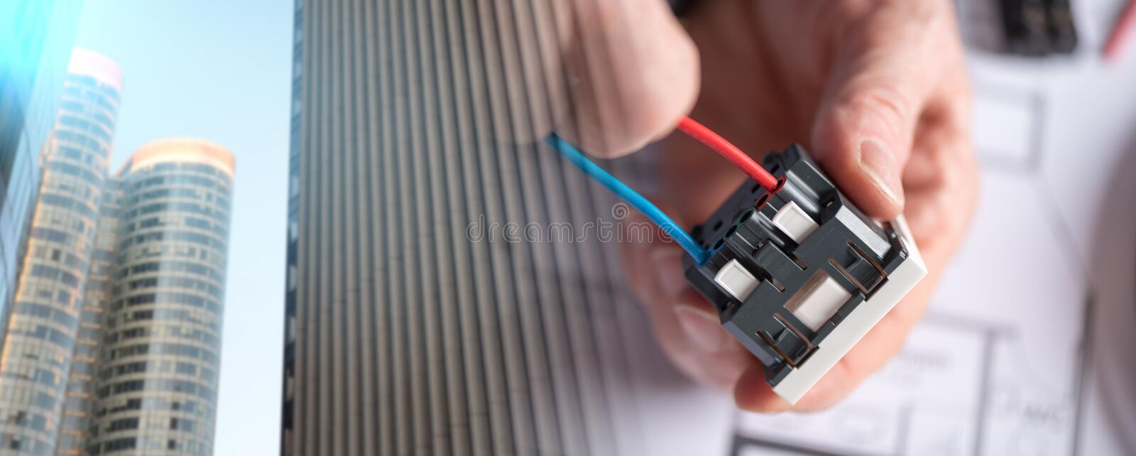 Electrician connecting a wire into a power socket; multiple expo. Electrician hands connecting a wire into a power socket; multiple exposure stock photo