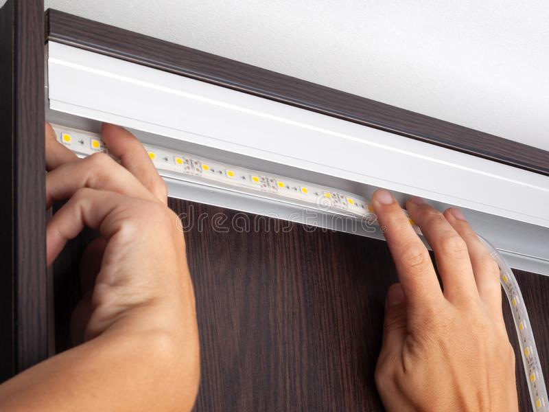 Electrician hands install LED strip lighting  in the niche of the cabinet to illuminate the wardrobe royalty free stock photos