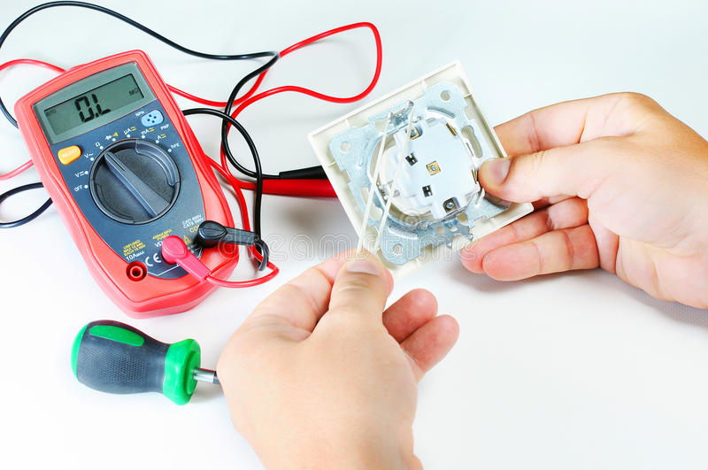 Electrician hands with socket. electricity and people concept. digital multimeter. screwdriver stock image