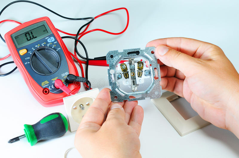Electrician hands with socket. electricity and people concept. digital multimeter. screwdriver royalty free stock images