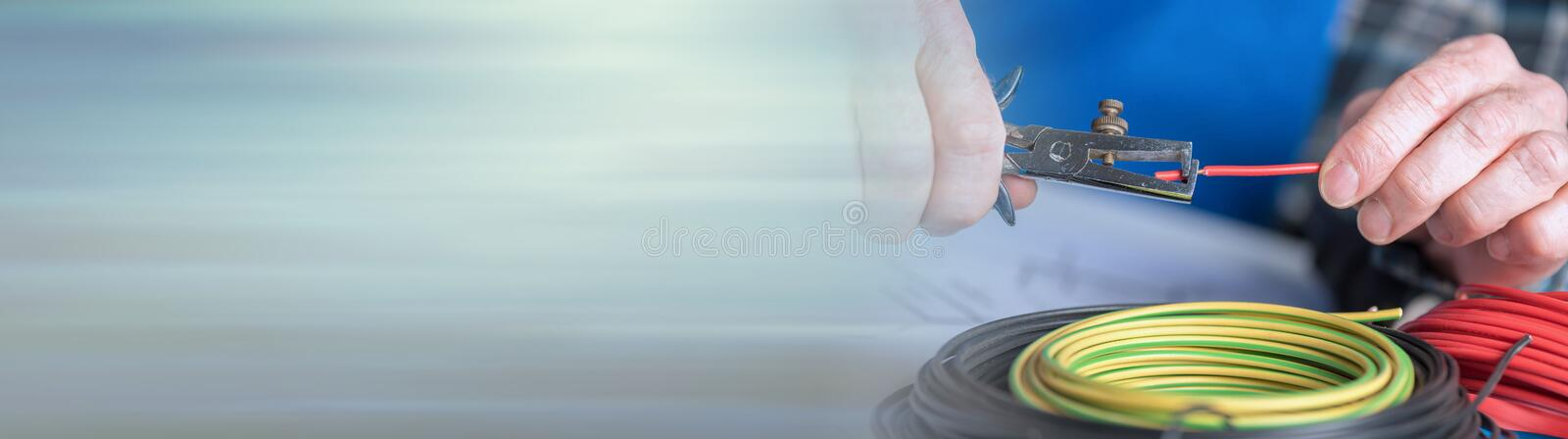 Electrician stripping a wire. panoramic banner royalty free stock image