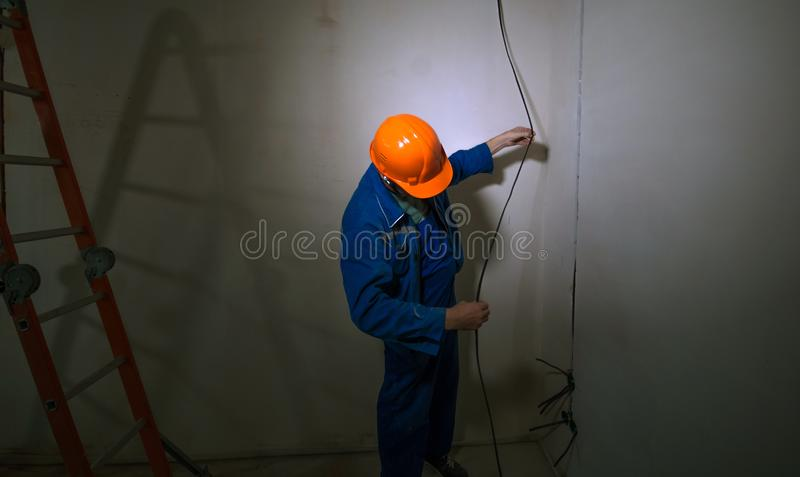 Electrician in hard hat and uniform holding a cable stock images