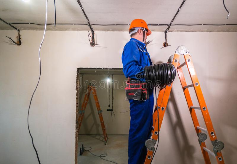 Electrician in hard hat and uniform holding a cable roll royalty free stock photography