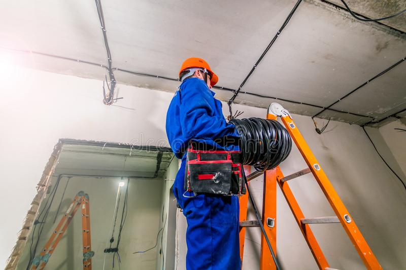 Electrician in hard hat and uniform standing on a ladder stock image