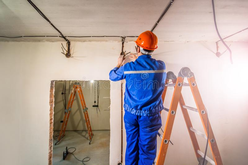 Electrician in hard hat and uniform standing on ladder royalty free stock images