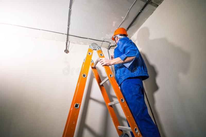 Electrician in hard hat and uniform standing on step ladder stock images