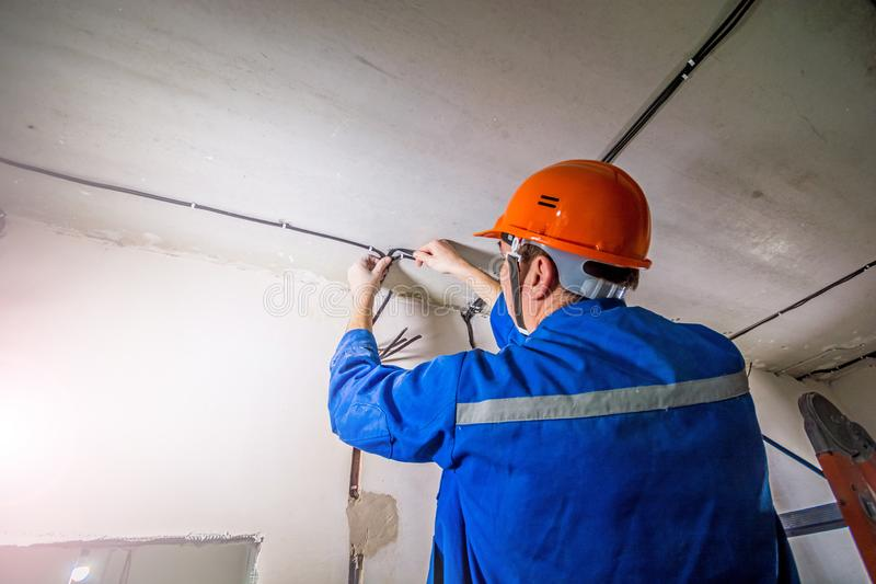 Electrician in hard hat and uniform working royalty free stock image