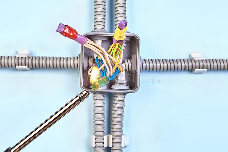 Electrician heats heat shrink tubing with lighter stock image