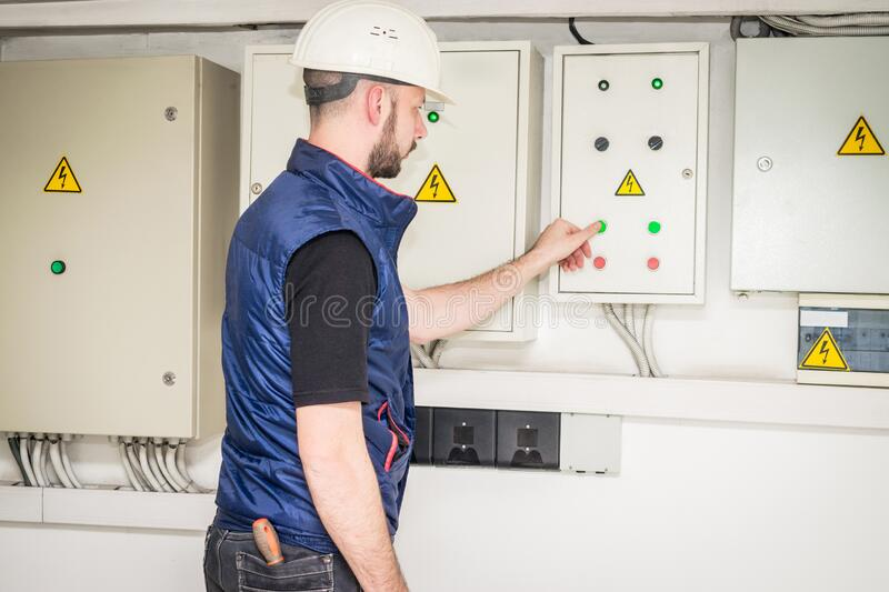 An electrician in a helmet presses the control panel buttons. The specialist works with powerful electric boxes. Engineer checks stock images