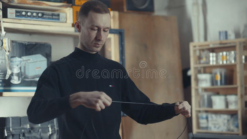 Electrician in his workshop twists black wires to make electrical stock photography
