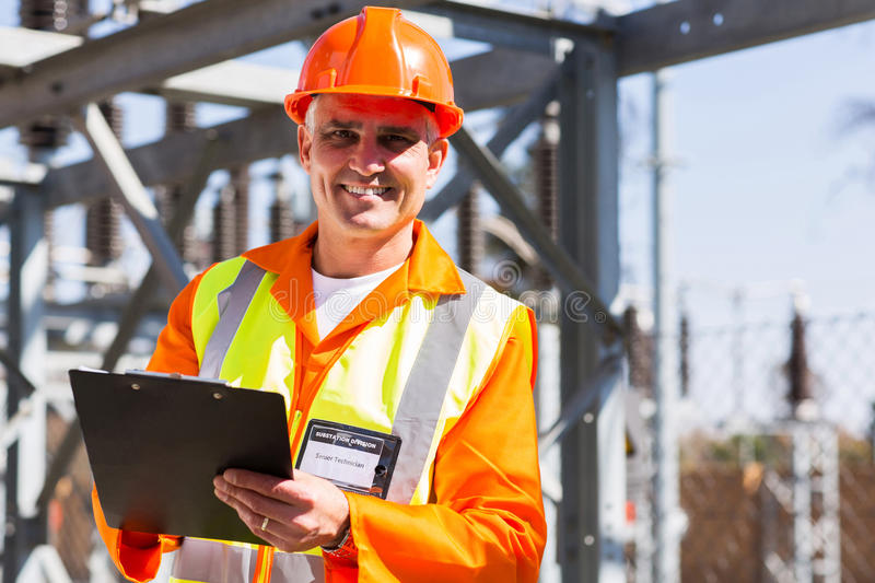 Electrician holding clipboard. Handsome middle aged electrician holding clipboard in electricity power plant stock images