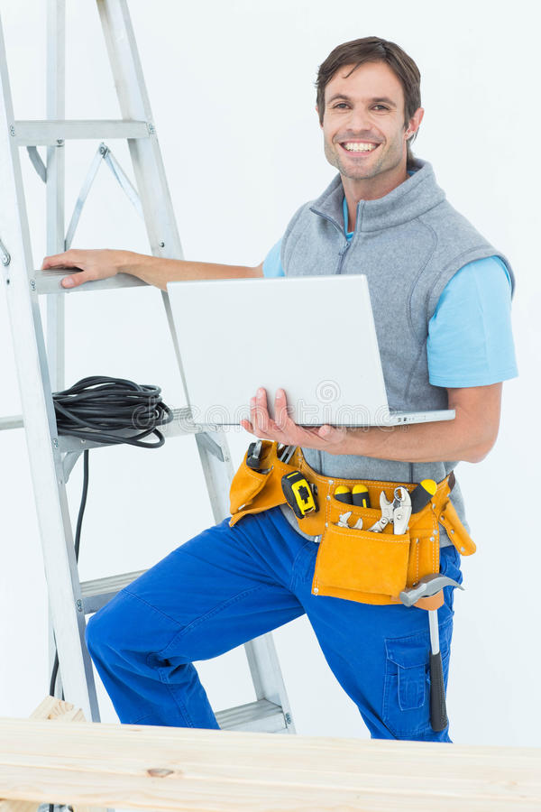 Electrician holding laptop by step ladder royalty free stock images