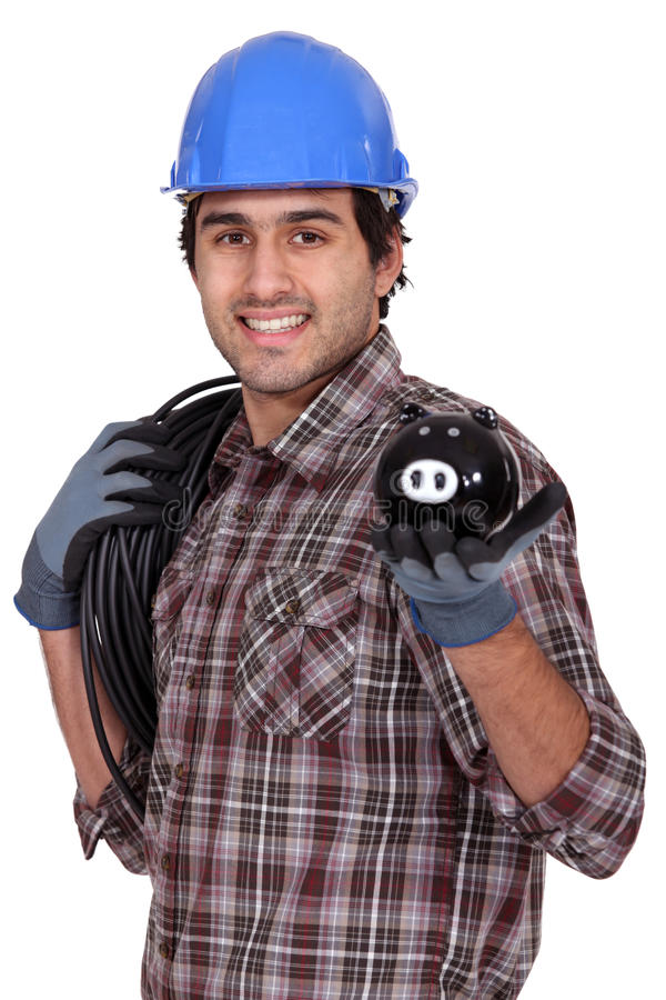 Electrician holding piggy-bank. Electrician proudly holding piggy-bank stock photography
