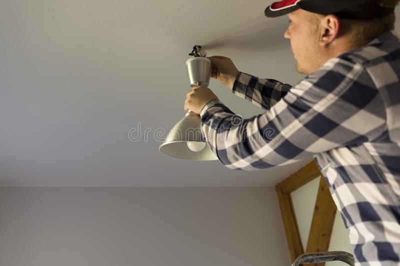 The electrician installs the ceiling lamp stock photos