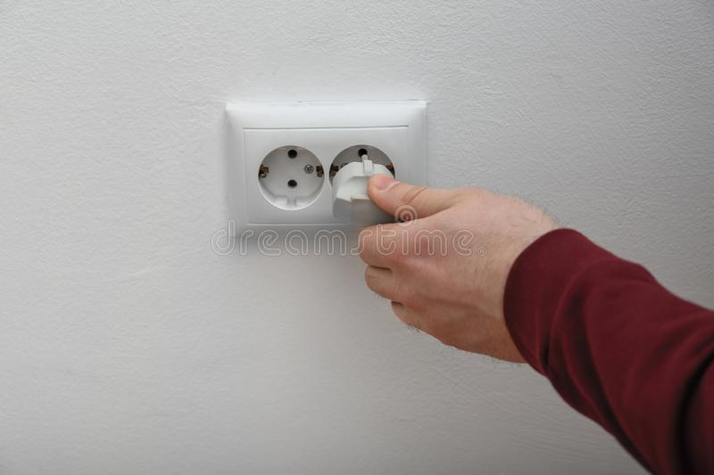 Electrician inserting plug into power socket on white background,. Closeup stock photo