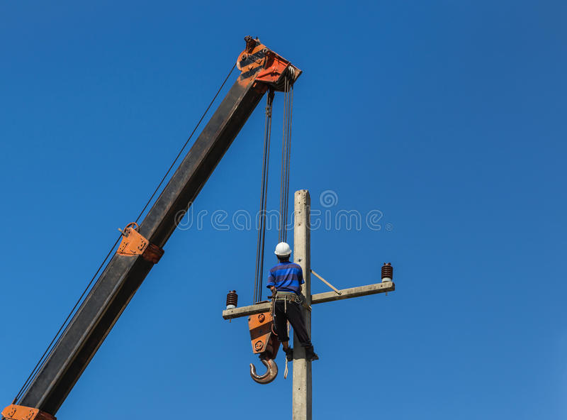 Electrician install wire on electric power pole with crane. Electrician install wire of the power line on electric power pole with crane royalty free stock photos