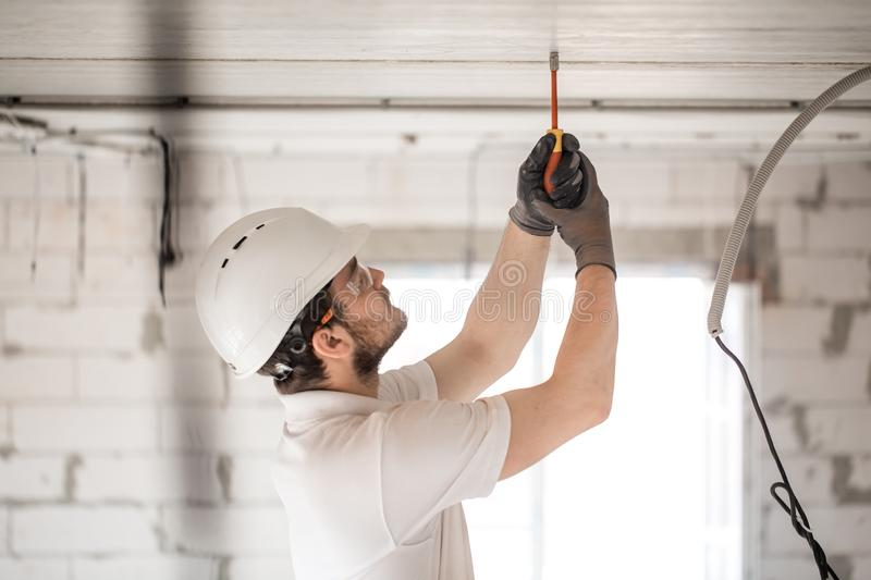 Electrician installer with a tool in his hands, working with cable on the construction site royalty free stock photos