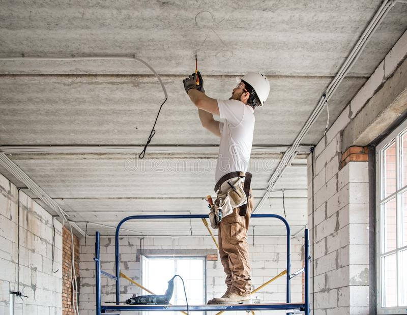 Electrician installer with a tool in his hands, working with cable on the construction site stock photos