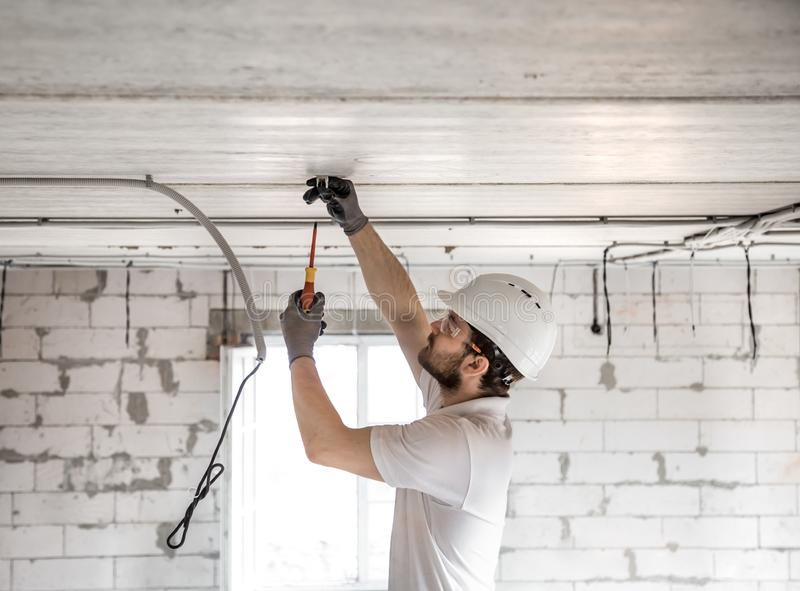 Electrician installer with a tool in his hands, working with cable on the construction site royalty free stock images