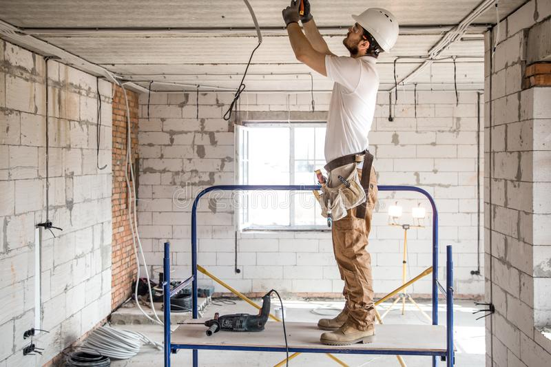 Electrician installer with a tool in his hands, working with cable on the construction site stock photography