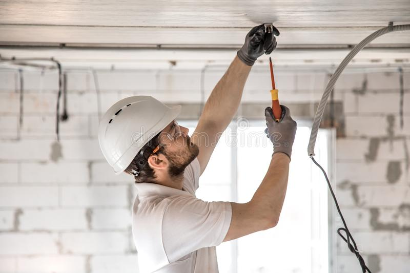 Electrician installer with a tool in his hands, working with cable on the construction site stock image