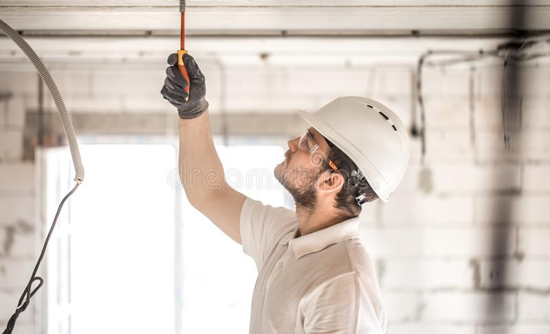 Electrician installer with a tool in his hands, working with cable on the construction site royalty free stock photography
